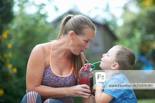 Junge und Mutter teilen sich einen frischen Smoothie im Garten