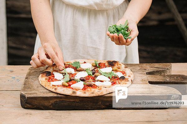 Frau legt Kräuter auf hausgemachte Pizza  Mittelteil