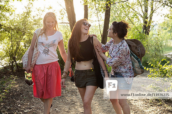 Three female friends walking through forest