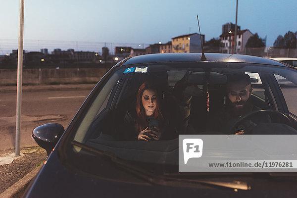 Paar im Auto in der Nacht mit Smartphone