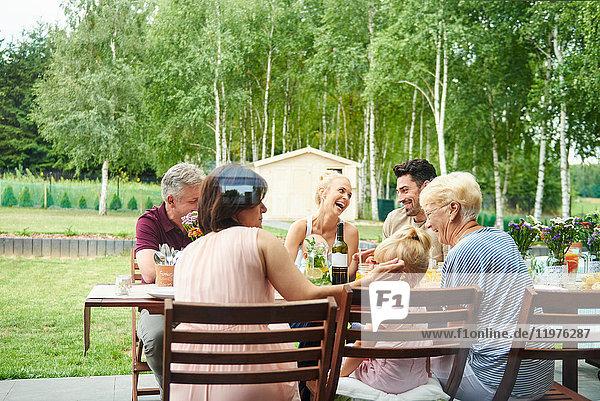 Drei-Generationen-Familie beim Mittagessen auf dem Terrassentisch