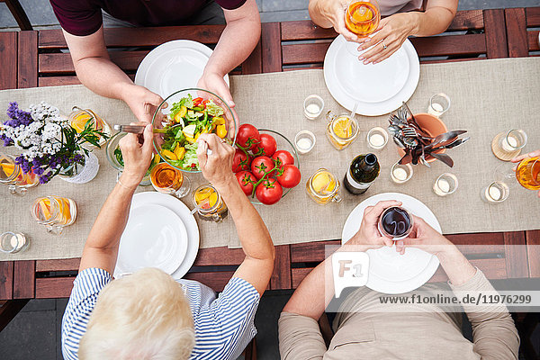 Draufsicht auf die Familie  die beim Familienessen auf der Terrasse Salate verteilt