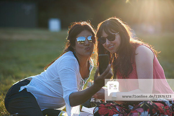 Two mature female friends taking smartphone selfie at festival in park  London  UK