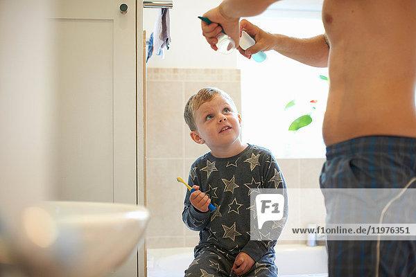 Junge im Badezimmer mit Vater  der sich zum Zähneputzen vorbereitet