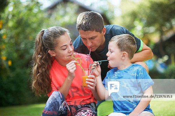 Reifer Mann mit Teenager-Tochter und Sohn teilen sich frischen Smoothie im Garten