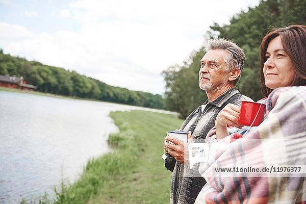 Reifes Paar steht in ländlicher Umgebung  hält heißes Getränk in der Hand  Frau in Decke gewickelt