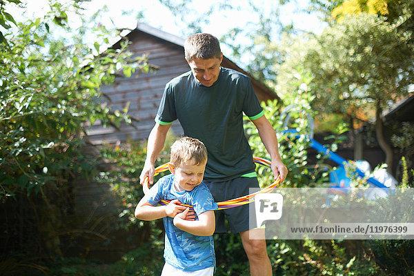 Junge und Vater spielen mit Kunststoffreifen im Garten