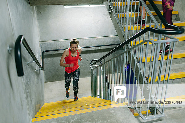 Young female runner running up indoor stairway