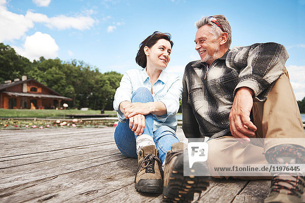 Reifes Paar entspannt sich auf Holzterrasse  lächelnd