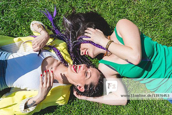 Frauen liegen lachend im Gras