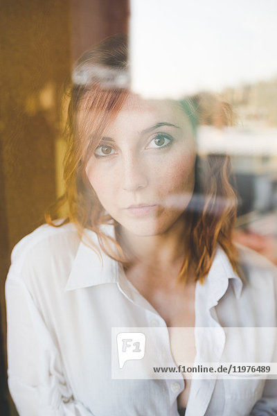 Portrait of beautiful young woman looking through window