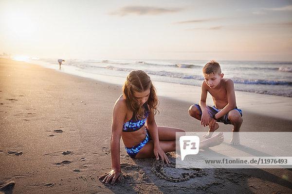 Mädchen malt Herz im Sand am Strand