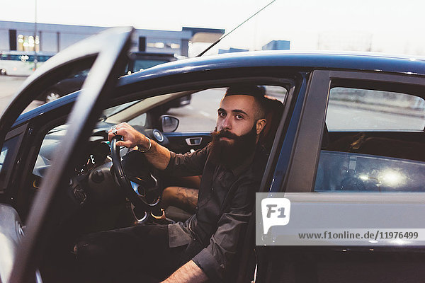 Bärtiger Mann im Auto schaut in die Kamera