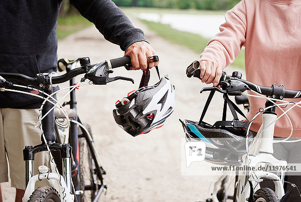 Ein erwachsenes Paar  das mit Fahrrädern den ländlichen Weg entlang fährt  mittlerer Abschnitt