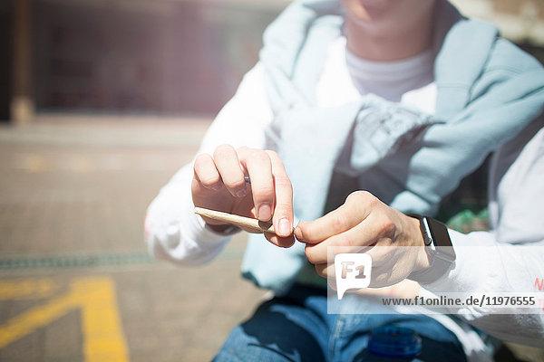 Junger Mann sitzt im Freien  dreht sich eine Zigarette  Mittelteil