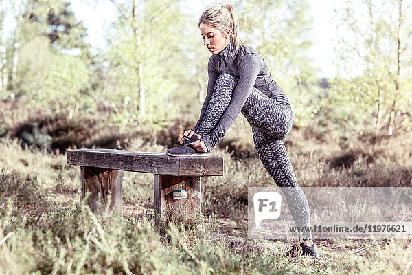 Young woman in rural setting resting foot on bench  tying shoe lace