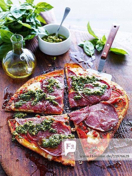 Geschnittene Salami- und Pesto-Pizza auf Servierbrett  erhöhte Ansicht