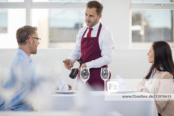 Kellner zeigt eine Flasche Wein zum Abendessen im Restaurant