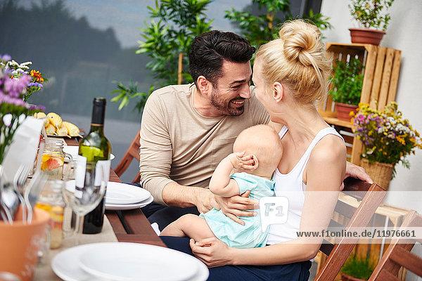 Glückliches Paar mit kleiner Tochter beim Familienessen auf dem Terrassentisch