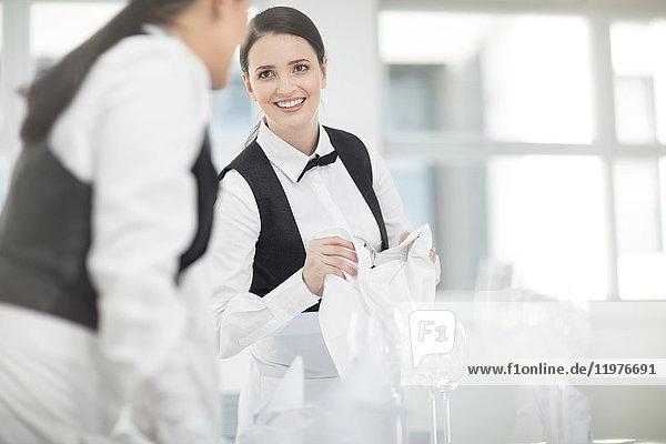 Zwei Kellnerinnen im Restaurant  die Tische vorbereiten