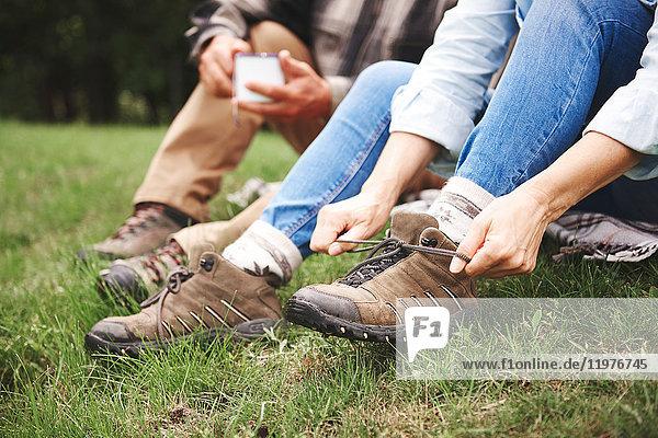 Auf Gras sitzendes reifes Paar  Frau bindet Wanderschuhe  niedriger Abschnitt