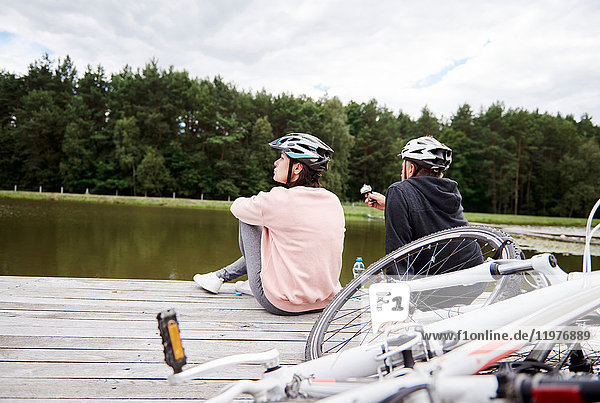 Ein erwachsenes Paar entspannt sich auf dem Steg  Fahrräder neben sich  Rückansicht