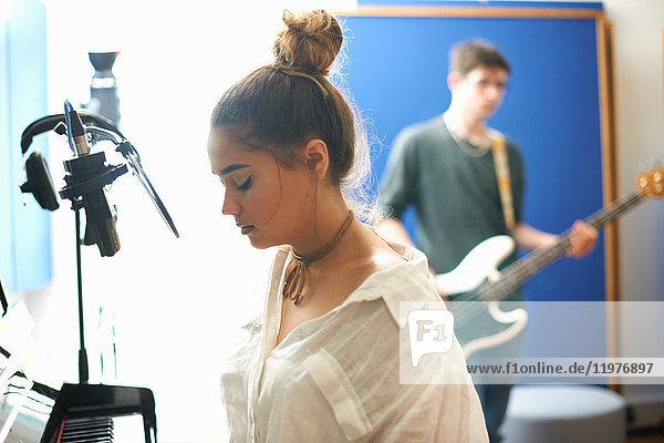 Junge Studentin bereitet sich im Aufnahmestudio auf das Singen vor