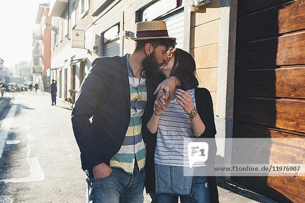 Romantisches Paar küsst sich auf sonnenbeschienener Straße