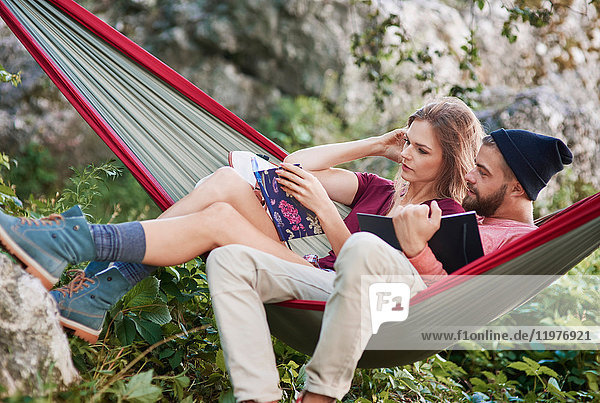 Couple relaxing in hammock reading books  Krakow  Malopolskie  Poland  Europe