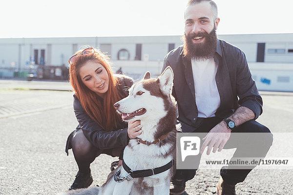 Paar streichelnder Hund lächelnd