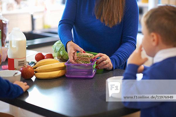 Ausschnitt einer Mutter  die in der Küche die Lunchbox ihrer Schulkinder packt