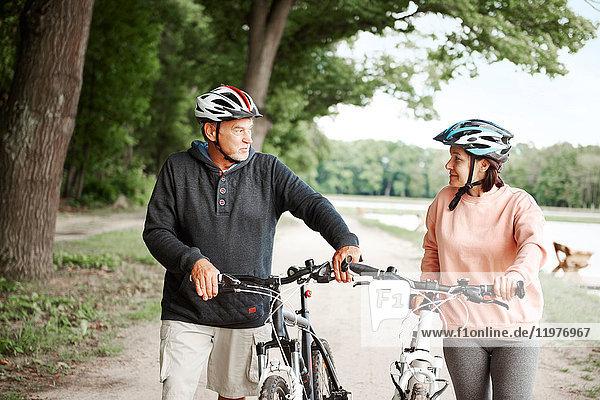 Ein erwachsenes Paar  das mit Fahrrädern einen ländlichen Weg entlang läuft