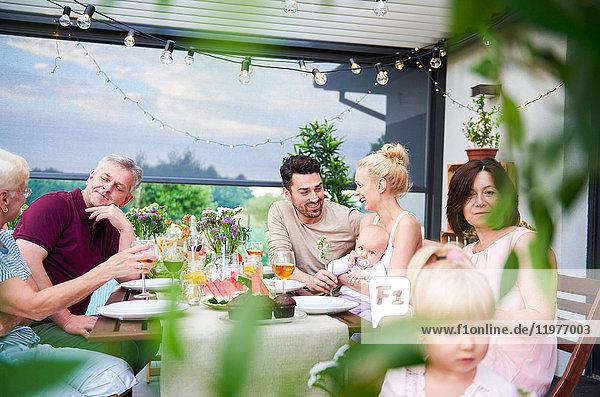 Drei-Generationen-Familie beim Mittagessen auf der Terrasse