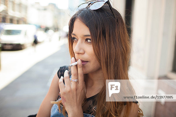 Young woman outdoors  smoking cigarette