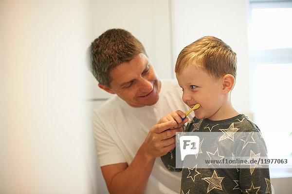 Reifer Mann zeigt Sohn beim Zähneputzen im Badezimmer
