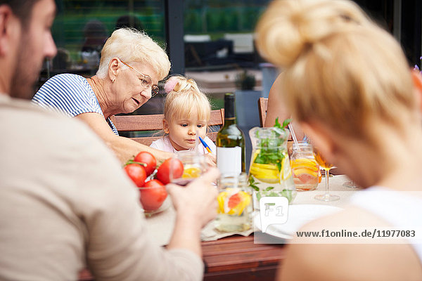 Senior woman with toddler granddaughter at family lunch on patio table