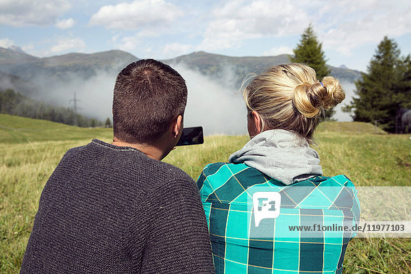 Rear view of couple in field photographing mist  Tirol  Steiermark  Austria  Europe