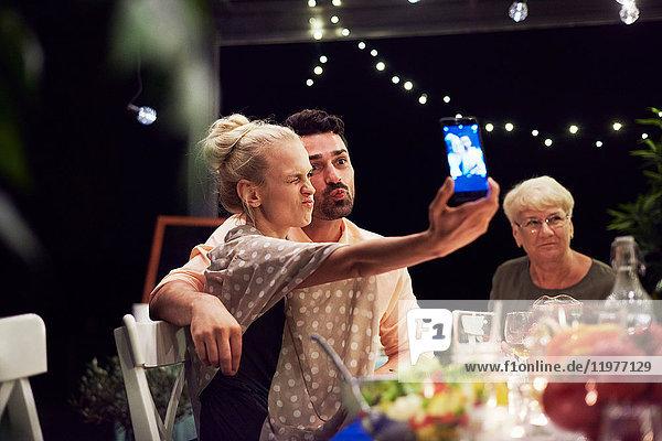 Gruppe von Menschen sitzt am Tisch  genießt die Mahlzeit  junge Frau nimmt sich selbst mit dem Smartphone