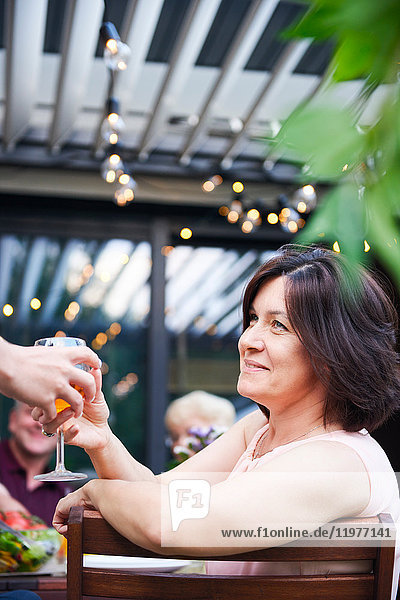 Reife Frau bekommt Wein beim Familienessen auf dem Terrassentisch gereicht