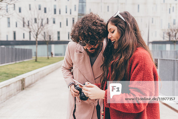 Young couple standing outdoors  looking at smartphone  laughing