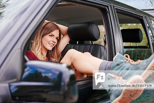 Woman in car with legs sticking out of window  Krakow  Malopolskie  Poland  Europe