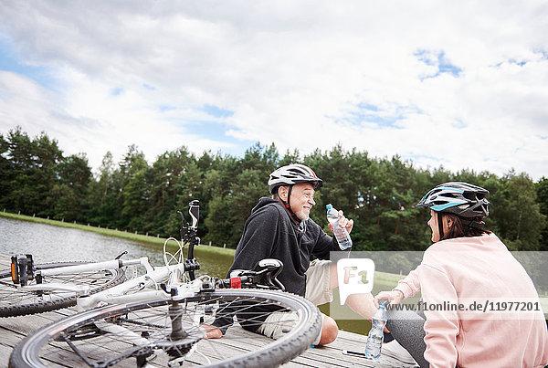Ein erwachsenes Paar entspannt sich auf einem Steg am See  mit Fahrrädern hinter sich