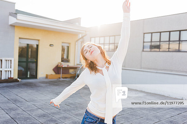 Beautiful young woman dancing on sunlit roof terrace with eyes closed
