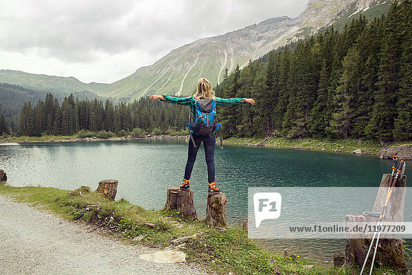 Rear view of woman balancing on rocks by lake  Tirol  Steiermark  Austria  Europe