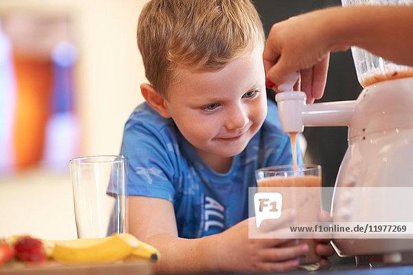Mutter gießt Frucht-Smoothie für Sohn in Küche