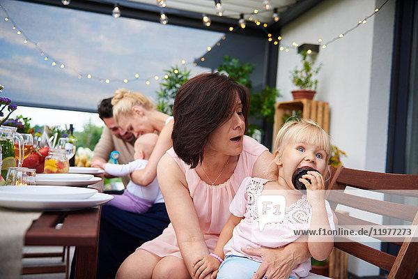 Reife Frau mit Kleinkind-Enkelin isst Brownie beim Familienessen auf der Terrasse
