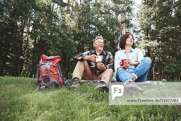 Ein erwachsenes Paar entspannt sich im Gras  hält Blechbecher  Rucksack daneben