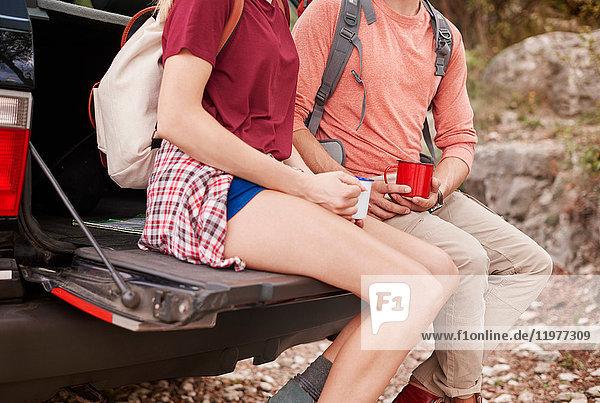 Schrägansicht eines Paares  das auf einem Kofferraum sitzt und Emaillebecher hält  Krakau  Malopolskie  Polen  Europa