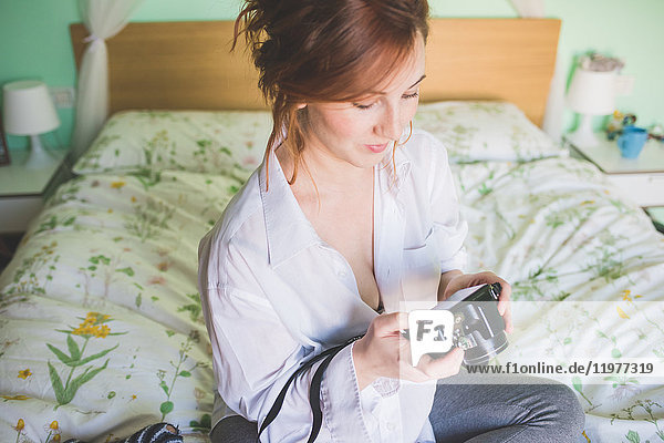 Young woman sitting on bed reviewing digital camera
