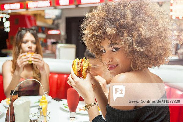 Drei junge Freunde sitzen im Diner und essen Burger